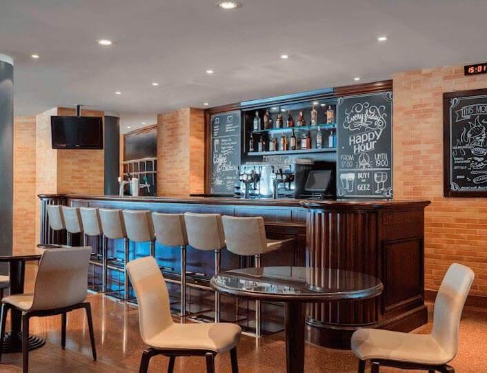 Gasten eten burger en drinken bier in Runway Café